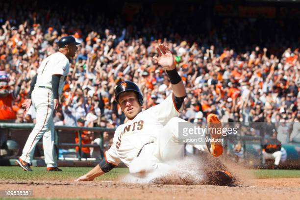 Buster Posey of the San Francisco Giants slides into home plate to score a run against the Colorado Rockies during the sixth inning at AT&T Park on...