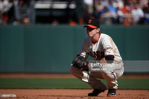 Buster Posey of the San Francisco Giants squats by first base during the ninth inning against the Los Angeles Dodgers on September 14 2014 at ATT...
