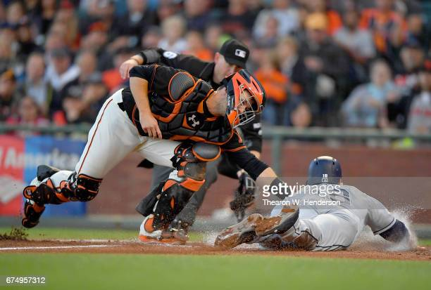 Buster Posey of the San Francisco Giants tags out Austin Hedges of the San Diego Padres attempting to steal home in the top of the fourth inning at...