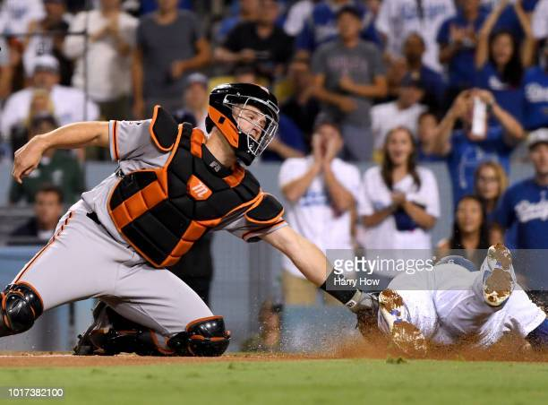 Buster Posey of the San Francisco Giants tags out Brian Dozier of the Los Angeles Dodgers during the fifth inning at Dodger Stadium on August 15 2018...