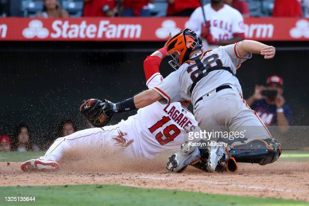 Buster Posey of the San Francisco Giants tags out Juan Lagares of the Los Angeles Angels at home plate in the 12th inning at Angel Stadium of Anaheim...