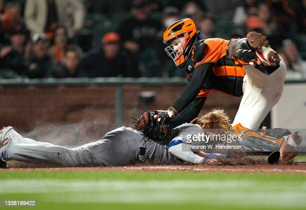 Buster Posey of the San Francisco Giants tags out Justin Turner of the Los Angeles Dodgers at home plate in the top of the 11th inning at Oracle Park...