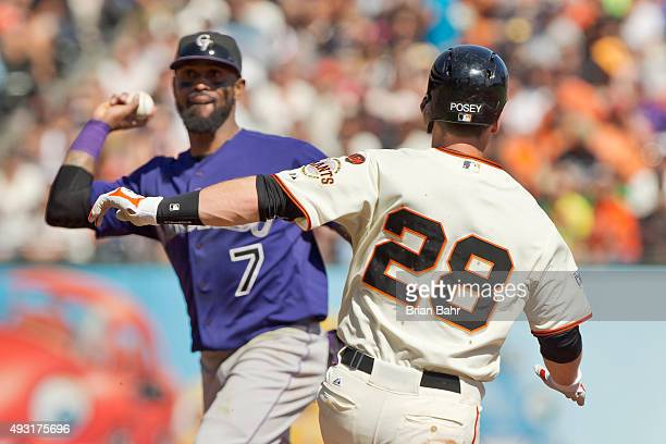 Buster Posey of the San Francisco Giants tries unsuccessfully to break up a double play against shortstop Jose Reyes of the Colorado Rockies in the...