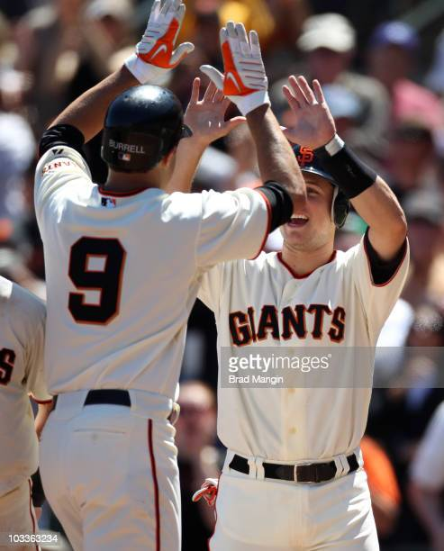 Buster Posey of the San Francisco Giants waits at home plate to greet teammate Pat Burrell after Burrell hit a grand slam against the Chicago Cubs...