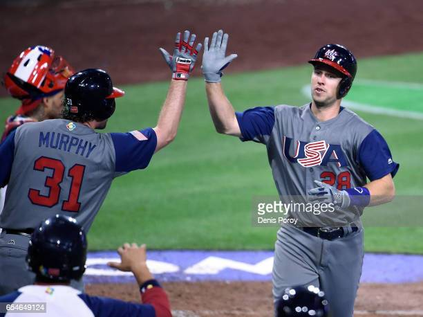 Buster Posey of the United States is congratulated by Daniel Murphy after hitting a solo home run during the fifth inning of the World Baseball...