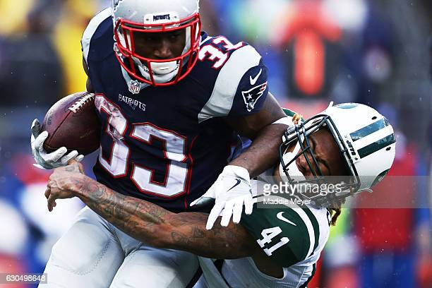 Buster Skrine of the New York Jets tackles Dion Lewis of the New England Patriots during the first half at Gillette Stadium on December 24 2016 in...