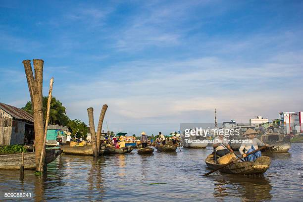 Bustling activity at Cai Rang floating market early in the morning under a blue sky with white clouds in the Mekong Delta south Vietnam