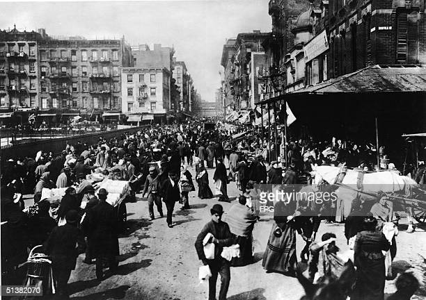 Bustling crowd of men and women shops among the market stalls on Hester Sreet, Lower East Side, New York, 1895.