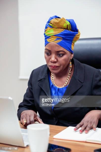 drukke afrikaanse zakenvrouw op kantoor - traditionele kledij stockfoto's en -beelden