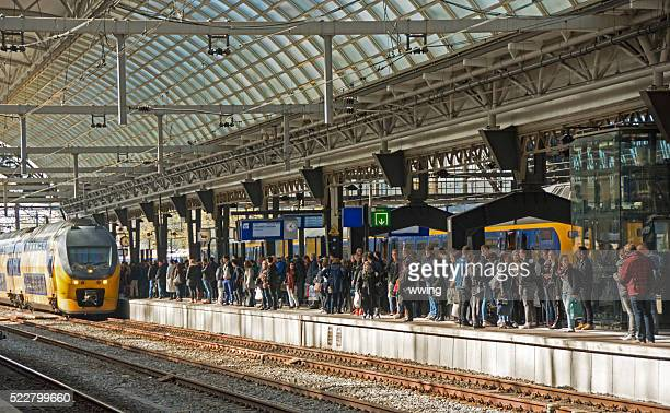 Busy Amsterdam Central Station with arriving train.