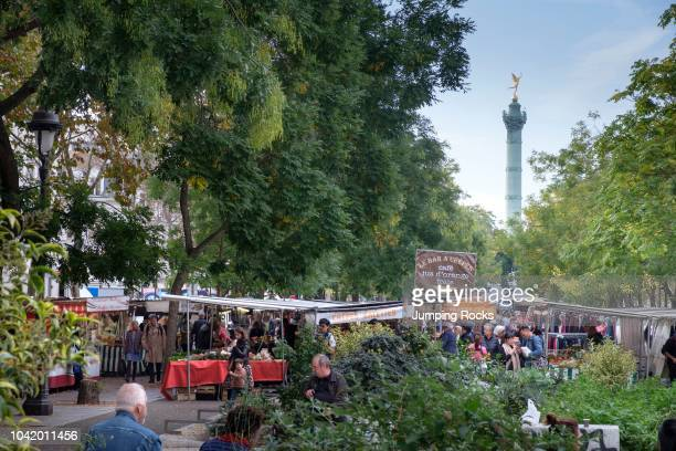Busy Bastille Market with shoppers and Bastille Monument in Background Paris France