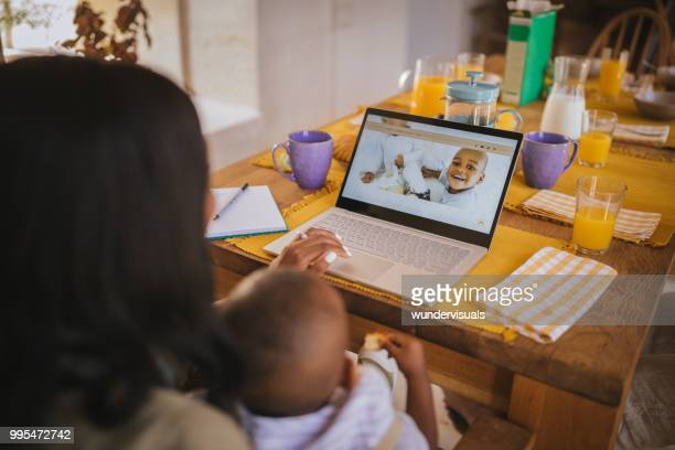 Busy blogger mother with children writing blog post at home