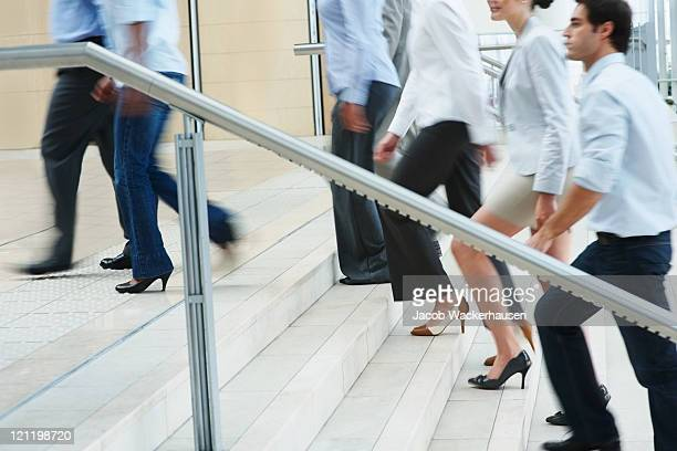 Busy business people ascending on office stairs