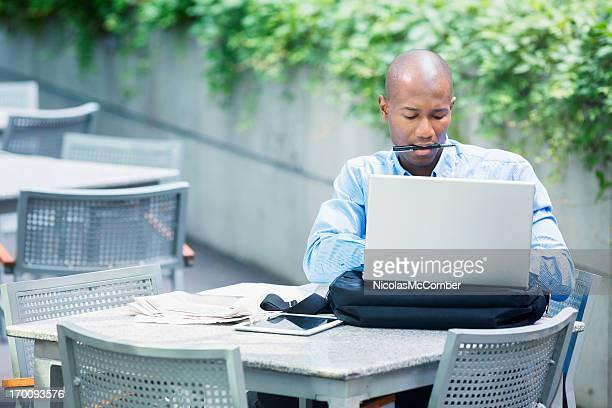 Homme d'affaires bien remplie de dactylographie sur ordinateur portable à l'extérieur