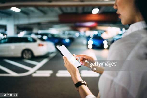 busy businesswoman checking mobile phone while walking to her car in car park - etagenparkhaus stock-fotos und bilder