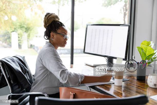 busy businesswoman concentrates while working at her desk - analysing stock pictures, royalty-free photos & images