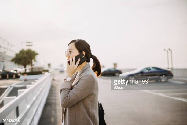 Busy businesswoman talking on mobile phone in outdoor car park in city