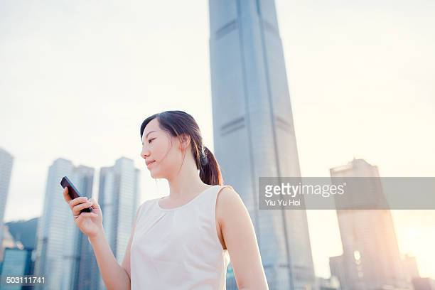 Busy businesswoman text messaging in modern city