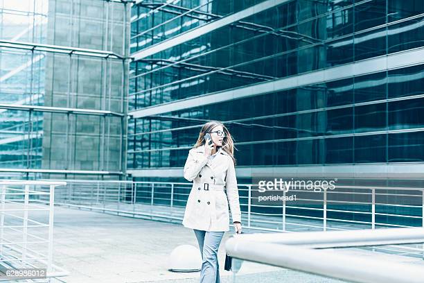 Busy businesswoman walking on street and talking on smart phone