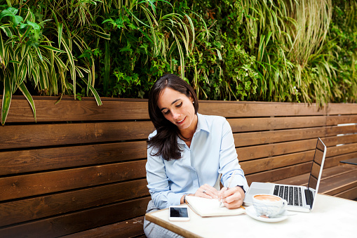 Busy businesswoman working at an outdoor cafe - gettyimageskorea