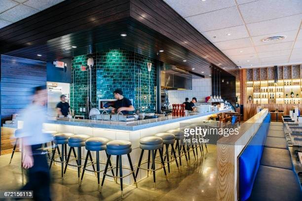 Busy Caucasian workers at counter in modern bar and restaurant