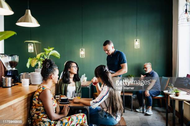 busy city cafe with customers and barista - coffee shop stock pictures, royalty-free photos & images