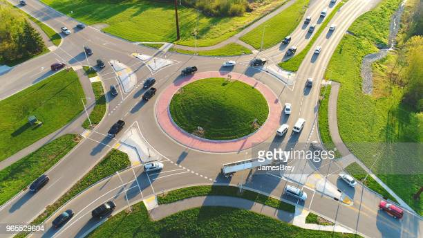 Busy city roundabout intersection at sunrise rush hour.