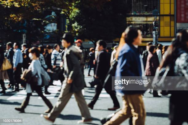 busy commuters crossing street during office rush hour in downtown district in tokyo - japan commuters ストックフォトと画像