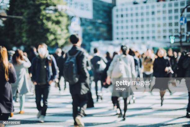 busy commuters crossing street in downtown district during office rush hours - japan commuters ストックフォトと画像