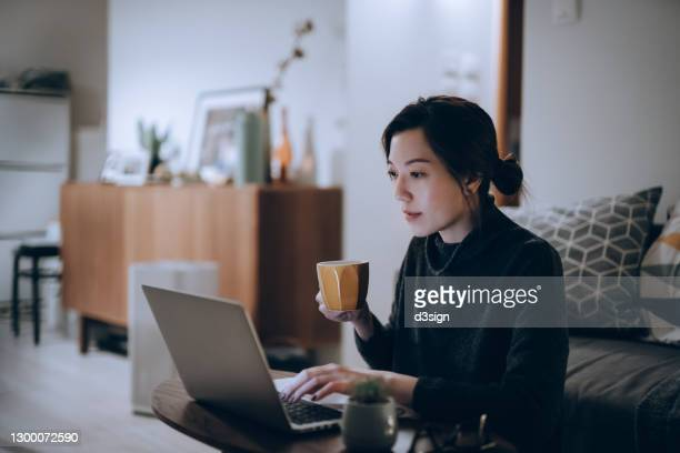 busy concentrated young asian woman working from home, working on laptop till late in the evening at home. home office, overworked, deadline and lifestyle concept - using laptop stock pictures, royalty-free photos & images