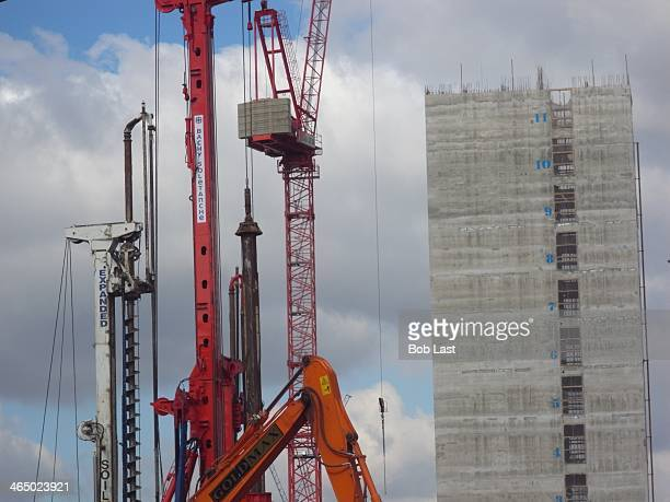 Busy construction site featuring a vibrant cluster of machinery and cranes reaching in to the sky