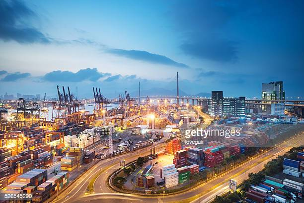 busy container terminal in twilight - heavy industry stock photos and pictures