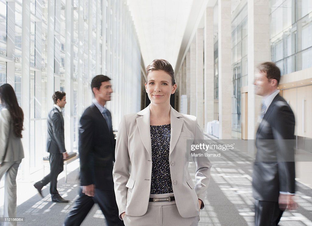 Busy co-workers waking past businesswoman : Stock Photo