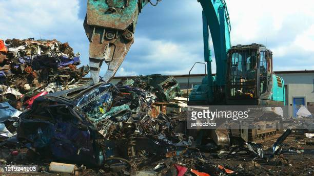 busy day at junkyard. mechanical claw dismantling old cars - dismantling stock pictures, royalty-free photos & images