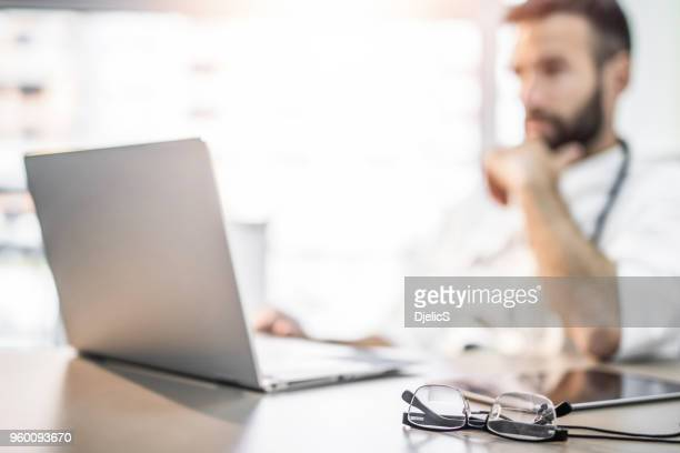 busy doctor's desk. - doctor stock pictures, royalty-free photos & images