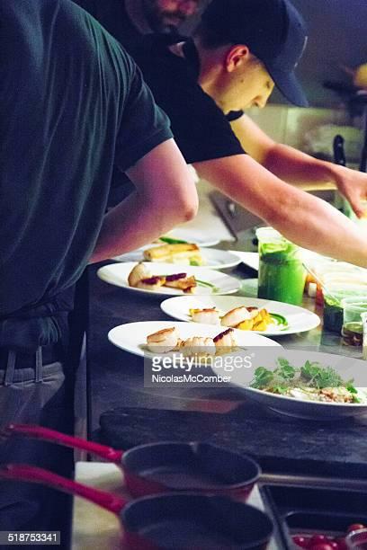 Soirée bien remplie dans la cuisine du restaurant avec des plats de chefs distribution des assiettes