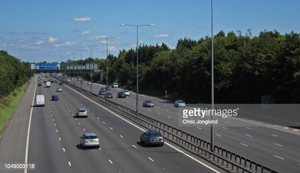 busy expressway through wooded countryside - motorway stock pictures, royalty-free photos & images