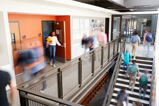 Busy High School Corridor During Recess With Blurred Students And Staff 976317922