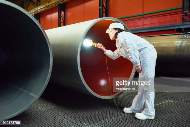 busy inspector examining manufactured tube - female flasher stock pictures, royalty-free photos & images