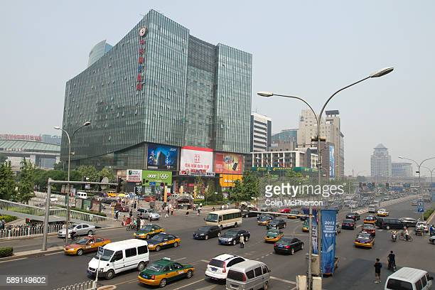A busy intersection with cars and taxis driving past the Zhongguancun eplaza Beijing China which sells reconditioned and repaired computers and other...