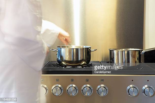 Busy Kitchen Stove with Pans and Chef