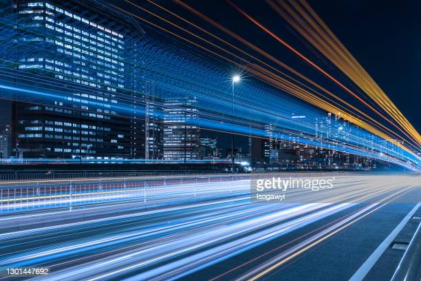 busy light trails and illuminated skyscrapers in tennozu isle at night - isogawyi stock pictures, royalty-free photos & images