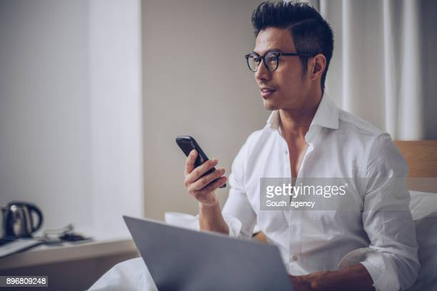 busy man in bedroom - handsome chinese men stock pictures, royalty-free photos & images