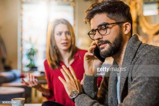 busy man on the phone ignoring his girlfriend. - fighting stance stock pictures, royalty-free photos & images