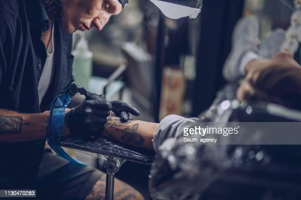 Vielbeschäftigter Mann Tattoo-Künstler