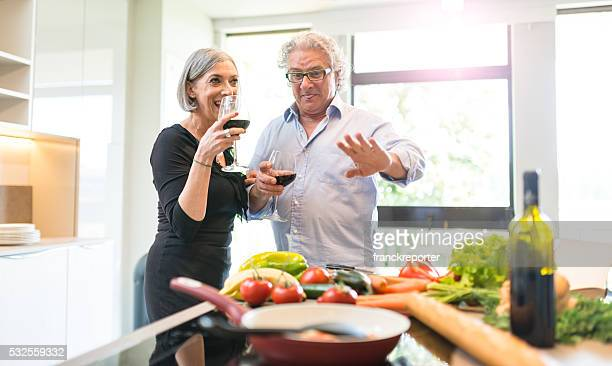 busy mature couple cooking in the kitchen