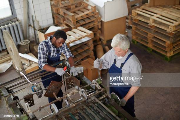Vielbeschäftigte Männer reparieren Druckmaschine