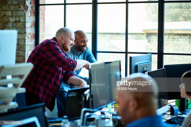 busy modern creative office with design professionals and computers - creative director stock pictures, royalty-free photos & images