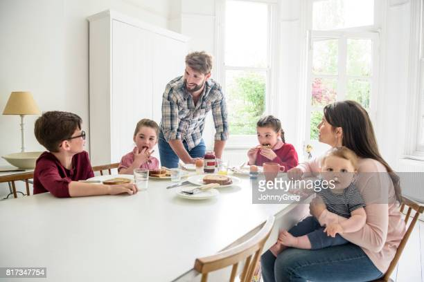 Busy modern family with two girls and two boys having breakfast at dining table