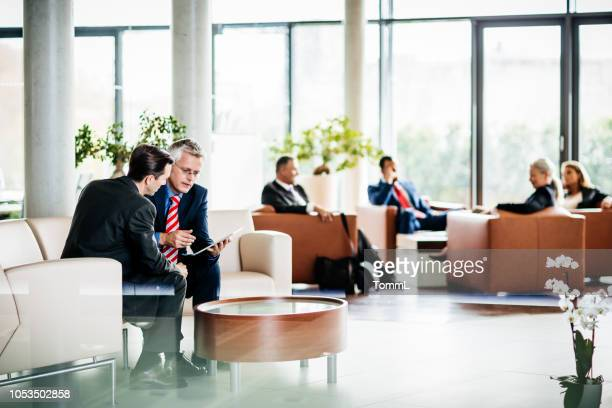 a busy, modern office waiting room - lobby stock pictures, royalty-free photos & images